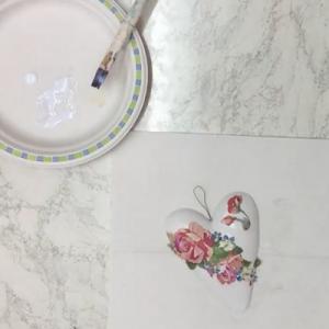 Białe serduszko z gipsu ozobione dekoracją w formie kwiatów. Nad nim talerzyk z pędzelkiem.