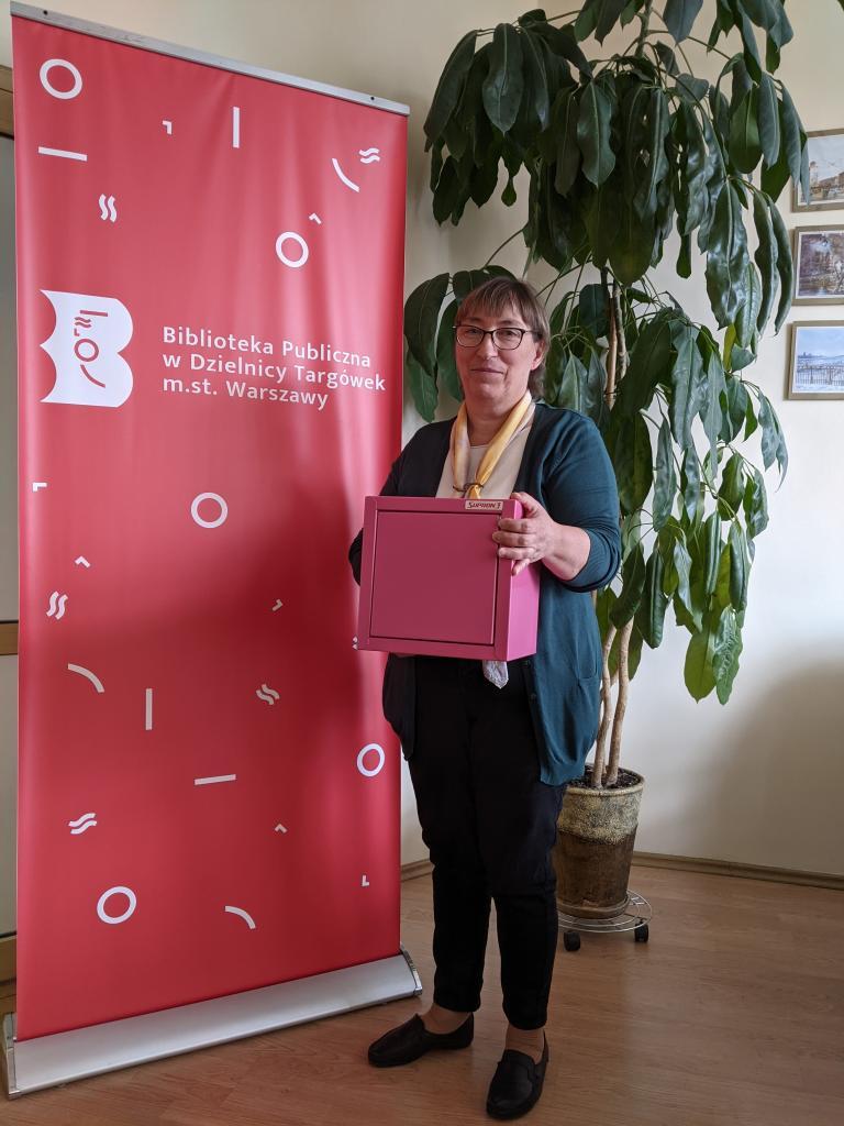 Dyrektor Biblioteki Publicznej w Dzielnicy Targówek m.st. Warszawy: Danuta Jankowska trzyma w dłoniach różową skrzyneczkę