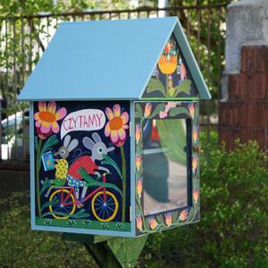 """Kolorowy, drewniany domek na książki postawiony na nóżce, na świeżym powietrzu. Na ściance domku malunek myszek jadących na rowerze. Nad nimi napis """"Czytamy""""."""