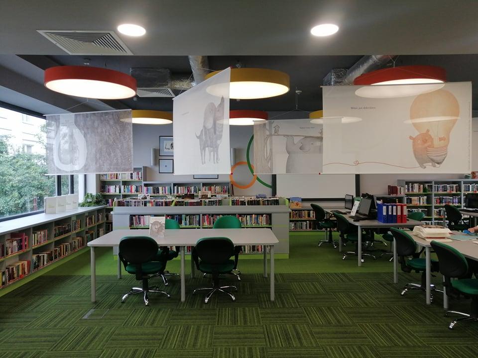 """Opis alternatywny: Widok na salę biblioteczną, pod sufitem zawieszone plansze wystawy z ilustracjami z książki """"Co robią uczucia?""""."""