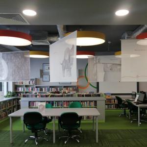 """Widok na salę biblioteczną, pod sufitem zawieszone plansze wystawy z ilustracjami z książki """"Co robią uczucia?""""."""