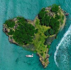 wyspa w kształcie serca (widok z góry), dookoła woda, w pobliżu wyspy statek