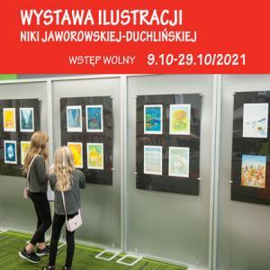 """Dwie dziewczynki stoją przed planszami wystawienniczymi, wpatrują się w szkice i ilustracje do książki """"Aliaszka"""". Na czerwonym tle, na górze znajduje się tekst: """"Wystawa ilustracji Niki Jaworowskiej-Duchlińskiej, wstęp wolny, 9.10-29.10/2021""""."""